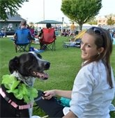 A woman and her dog enjoy a concert at Cortesi Veterans Memorial Park.