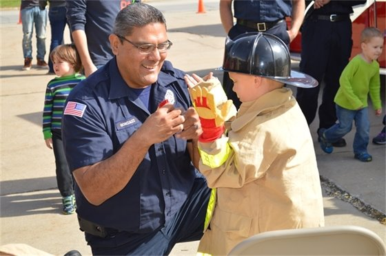 Firefighter Steve Gonzalez helps a young boy try on firefighter gear at the 2015 Villa Park Fire Prevention Week Open House