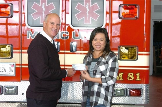 Villa Park Fire Chief Ron Rakosnik accepts a check from Theresa Bauer of Barks and Boots for the purchase of a AED.