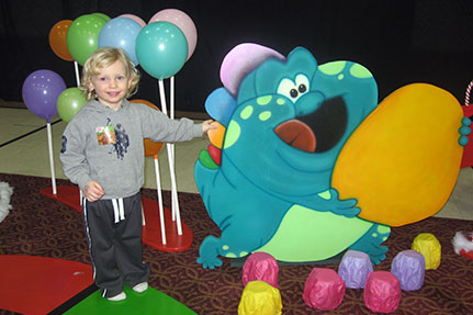 Child Standing Next to Candy Land Creature