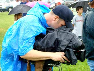 Camera Man Keeping His Equipment Dry