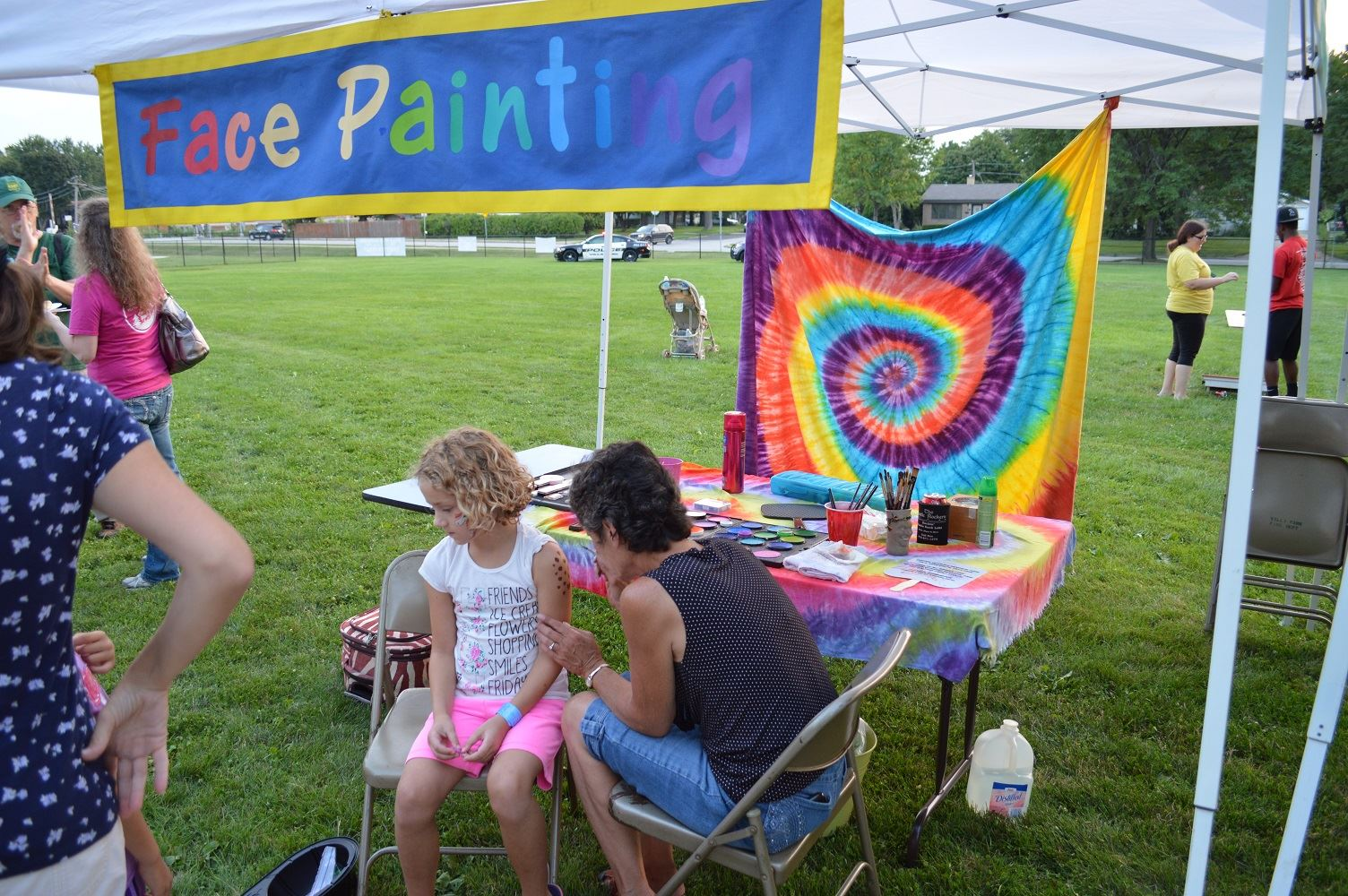 A young girl gets her arm painted at a National Night Out event at the Iowa Community Center, Aug. 2.