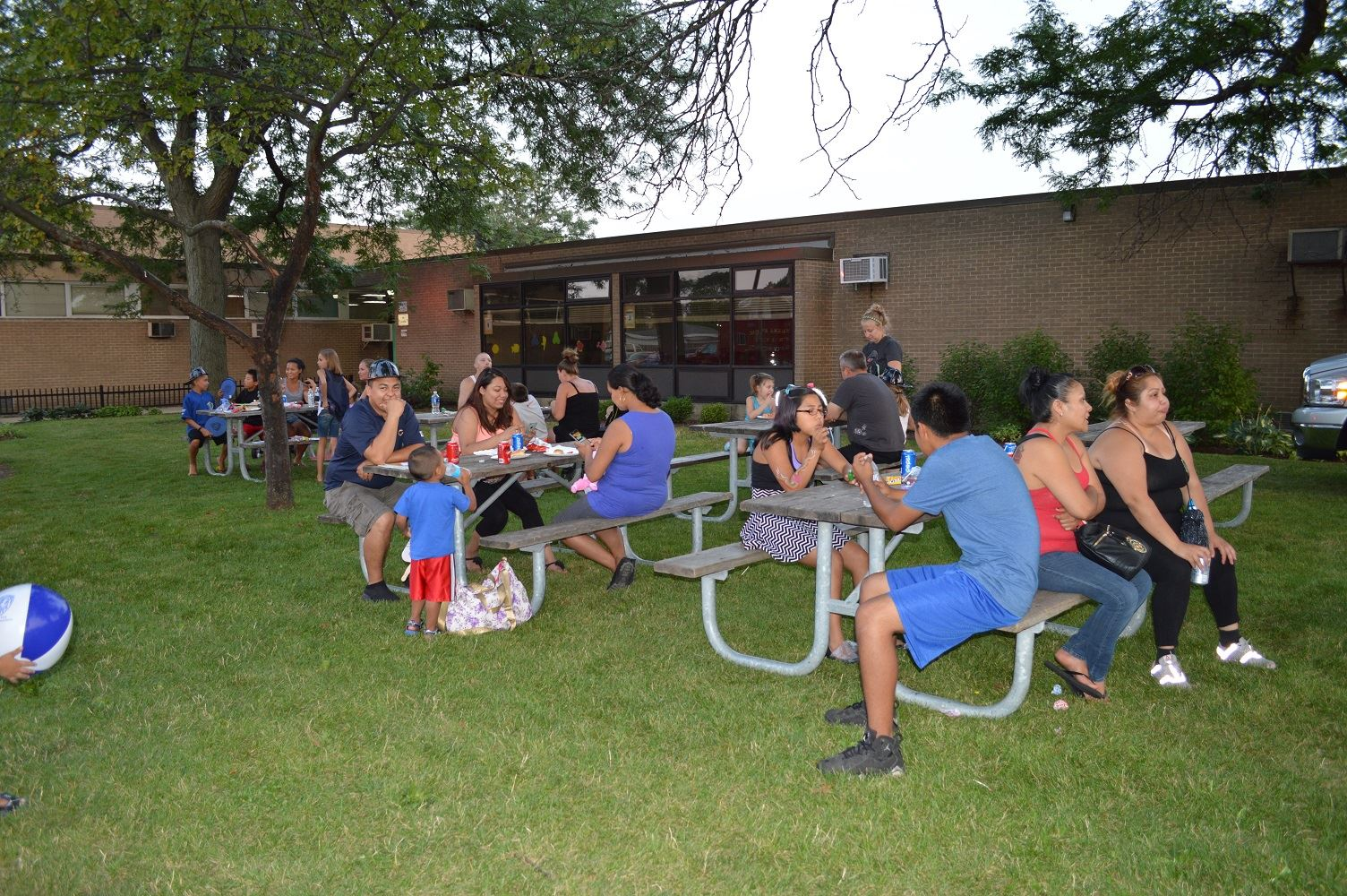 Community members enjoy food at picnic tables during a National Night Out event at the Iowa Community Center, Aug. 2.