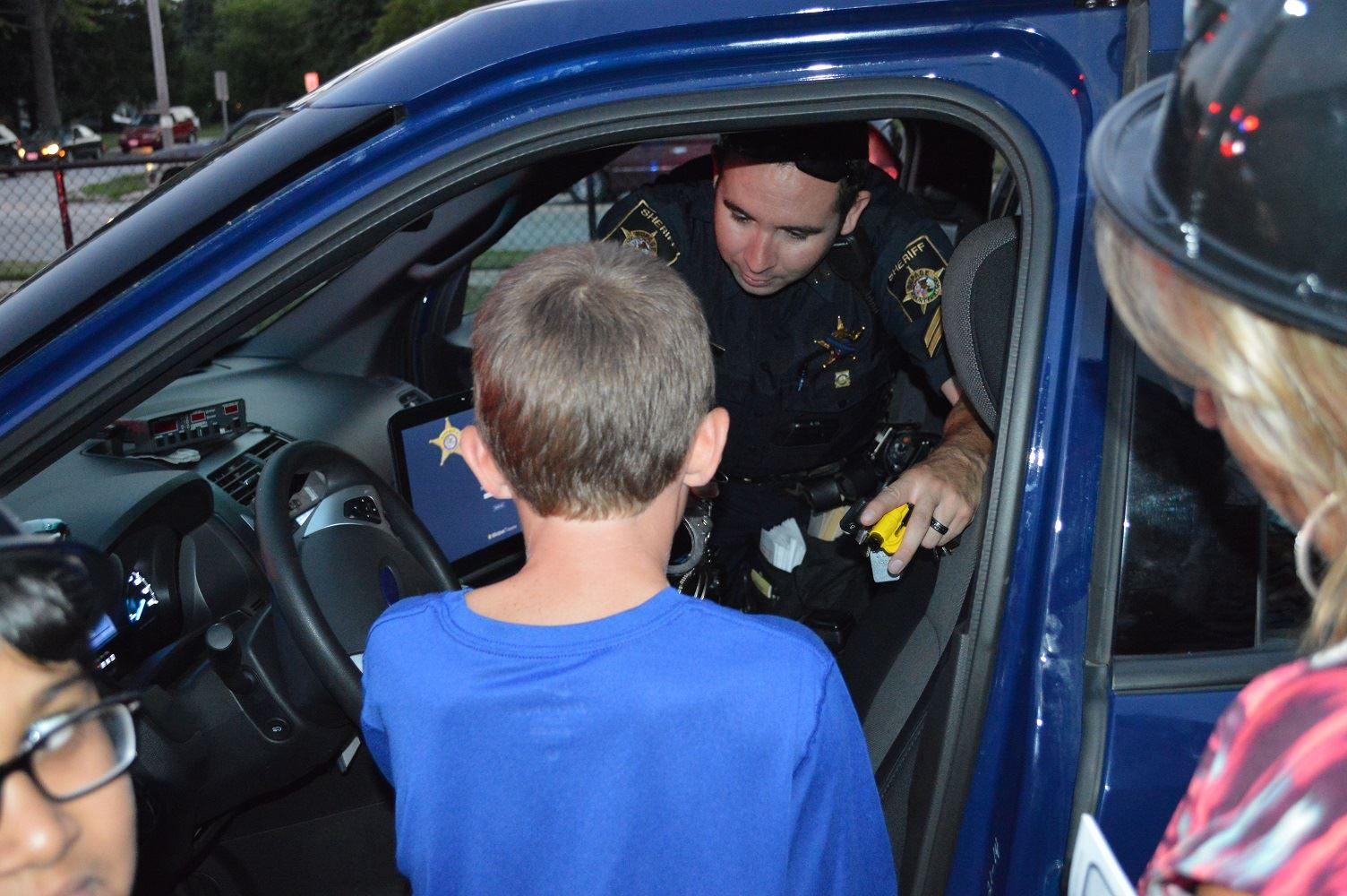 Families gather around a DuPage County Sheriff's vehicle during a National Night Out event at the Iowa Community Center, Aug. 2.