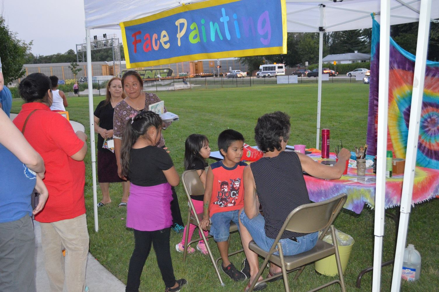 Kids line up to get their faces and arms painted during a National Night Out event at the Iowa Community Center, Aug. 2.