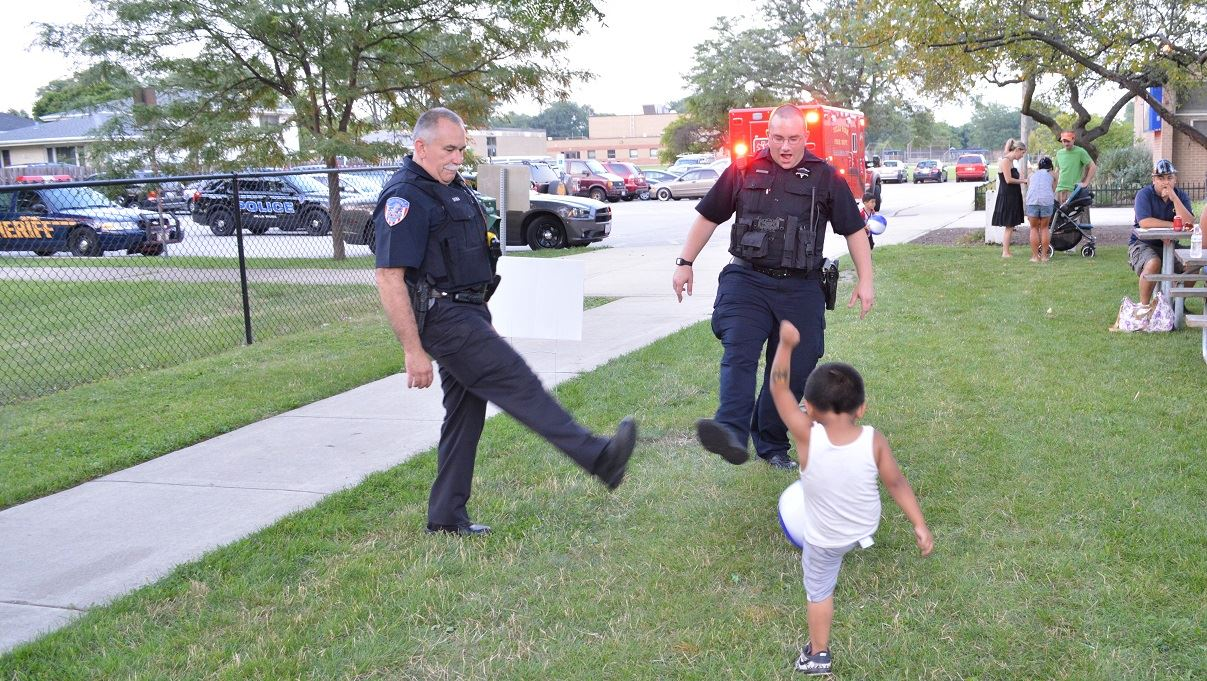 A pair of Villa Park Police Officers kick a ball around with a young boy at a National Night Out event at the Iowa Community Center, Aug. 2.