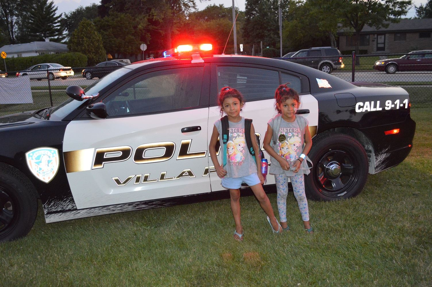 Two young girls pose for a photo in front of Villa Park Police car at a National Night Out event at the Iowa Community Center, Aug. 2.