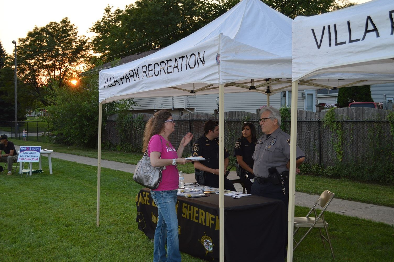Village President Deborah Bullwinkel talks with members of the DuPage County Sheriff's Department at a National Night Out event at the Iowa Community Center, Aug. 2.