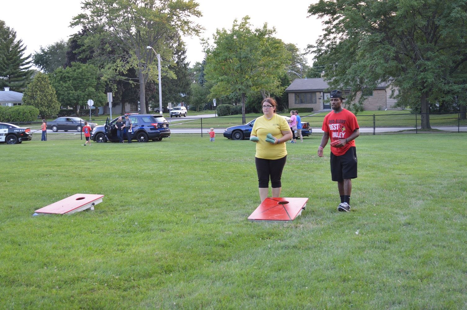 Community members play a game of bags at a National Night Out event at the Iowa Community Center, Aug. 2.